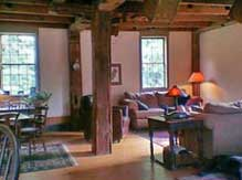 The living room with hand-hewed beams at the Grist Mill House