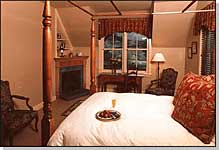 Second Floor. Overlooking the Gardens, a bright ivory and amber one-room suite furnished with an antique king-sized Sheraton four-poster, red and gold Anichini fabrics, gas fireplace and thermal massage tub for 2 in the sky-lighted bathroom